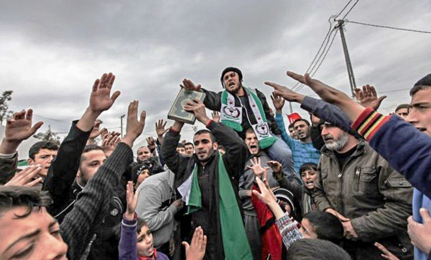 Syrian refugees, one of them holding copy of the Koran, shout Islamic slogans against Assad at Boynuyogun refugee camp in Hatay province in Turkey. Syrian border March 16, 2012.